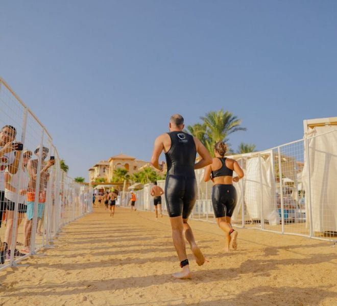 man and a woman running in the sand at sahl hasheesh